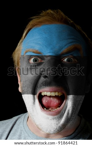 Low key portrait of an angry man whose face is painted in colors of estonia flag