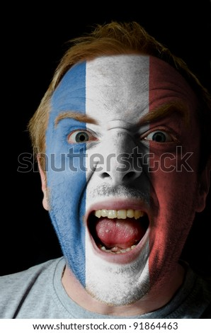 Low key portrait of an angry man whose face is painted in colors of france flag