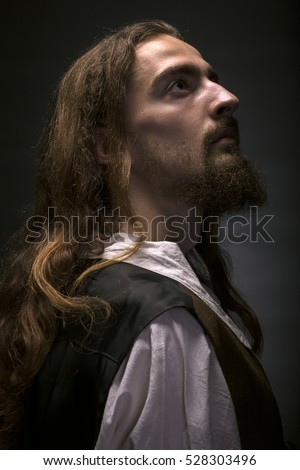 low key portrait of bearded medieval peasantin profile