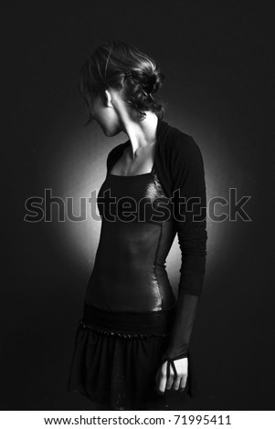 Low-key portrait of beautiful  model against black background - stock photo
