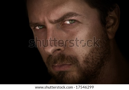 Low-key portrait of man with mysterious eyes - stock photo