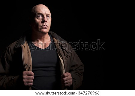 Low key portrait of mature serious looking bald headed man. Conveys look of mild aggression, or that of someone about to take off his coat. - stock photo