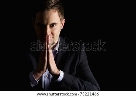 Low-key portrait of modern smiling business person in dark suit with folded hands in front of mouth looking straight, isolated on black background with copy-space. - stock photo