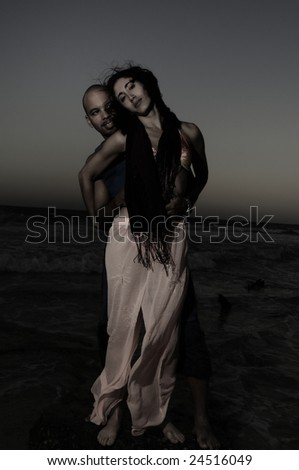 Low key portrait of young couple standing against ocean background at sunset - stock photo