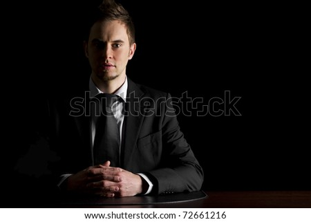 Low-key portrait of young serious businessman in dark suit sitting at office desk looking straight, isolated on black background with copy-space. - stock photo