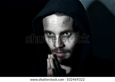 Low key portrait young man praying on the dark background. - stock photo