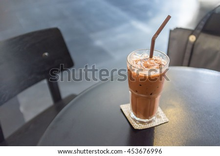 Low key shot of glass of iced latte milk coffee on table in dark room, blurred background - stock photo
