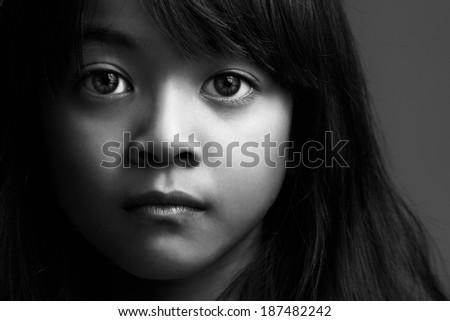 Low key shot of little asian girl in black & white - stock photo