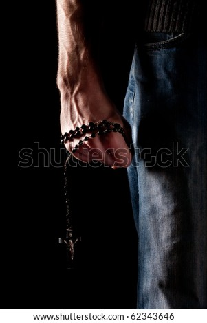 Low key shot or a man's arm gripping a rosary - stock photo