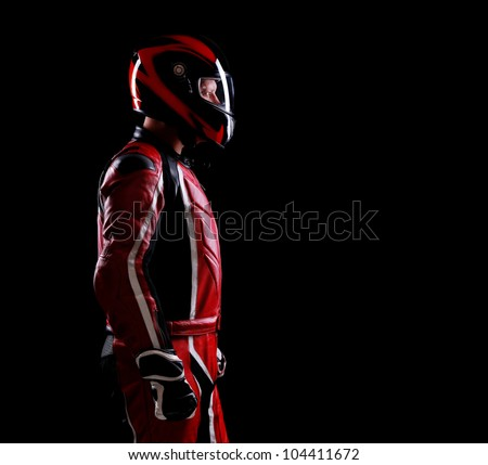 Low key silhouette of a biker standing on black background