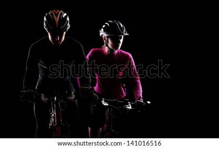 low key silhouette of a man and a  girl cyclists riding  bicycles on black background - stock photo