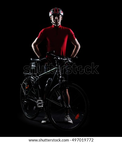 Low key silhouette of a mountain biker with his bicycle in a black studio