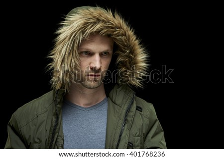 Low key studio portrait of young adult caucasian model wearing winter coat with hood on. - stock photo