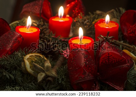 Low-key studio shot of a nice advent wreath with baubles and four burning red candles - stock photo