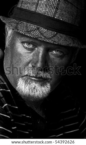Low light black and white photo of a bearded man - stock photo