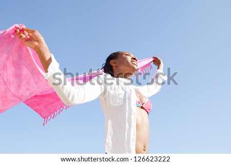 Low perspective of an attractive black woman holding a pink sarong up in the air against a deep blue sky background. - stock photo