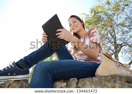 Low perspective view of a young woman using a digital tablet and touching the screen while sitting on a stone wall in a park with a blue sky.