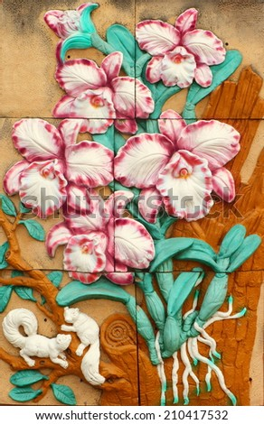 Low relief cement Thai style handcraft of orchid on wall. - stock photo