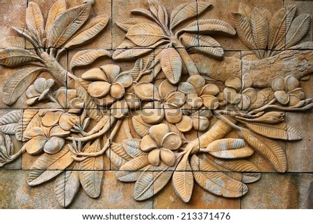 Low relief cement Thai style handcraft of plumeria or frangipani flowers  on wall - stock photo