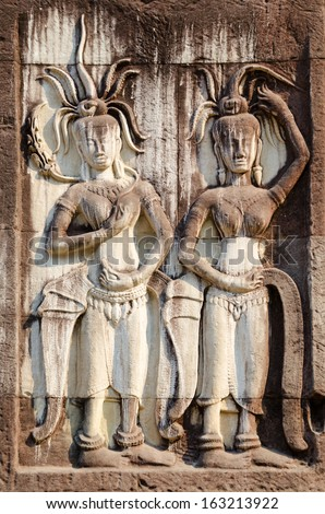 low relief in Angkor - two female statues in crowns - Apsarases, female spirits of clouds and waters in Hindu and Buddhist mythology