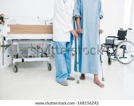 Low section of a doctor helping patient in crutches at the hospital