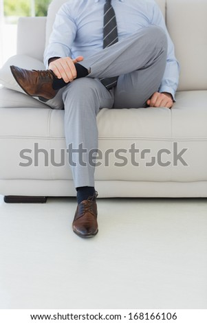 Low section of a well dressed relaxed young man sitting on sofa in the house - stock photo