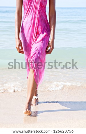 Low section of a woman on a beach, walking out of the sea wearing a bright pink sarong around her body while on vacations. - stock photo