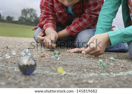 Low section of brother and sister playing marbles on playground - stock photo