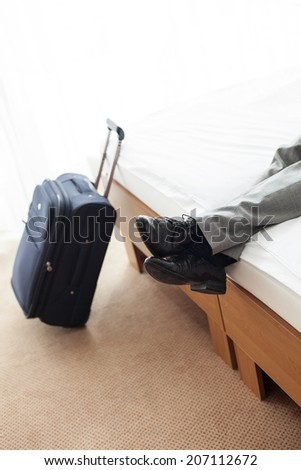 Low section of businessman lying on bed with luggage on floor in hotel room - stock photo