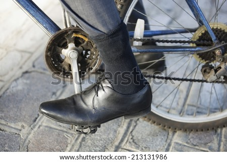 Low section of businessman riding bicycle on street - stock photo