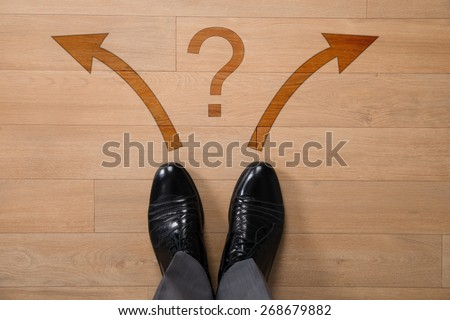 Low section of businessman standing in front of left or right arrows and question mark on floor - stock photo