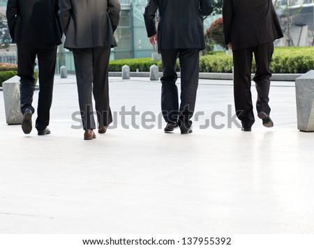 Low section of businesspeople walking together.