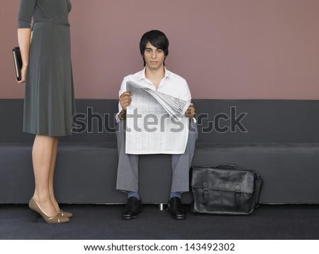 Low section of businesswoman standing by businessman reading newspaper in lobby - stock photo