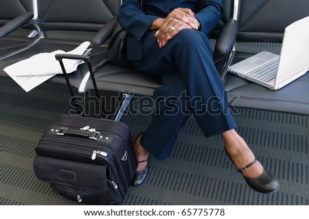 Low section of businesswoman with luggage and laptop - stock photo