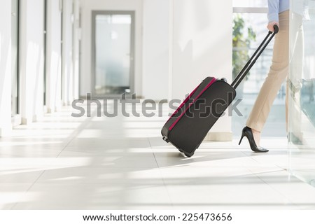 Low section of businesswoman with luggage leaving airport - stock photo