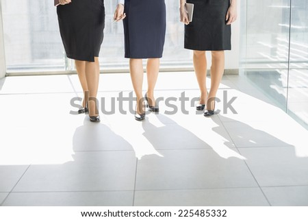 Low section of businesswomen standing on tiled floor in office - stock photo
