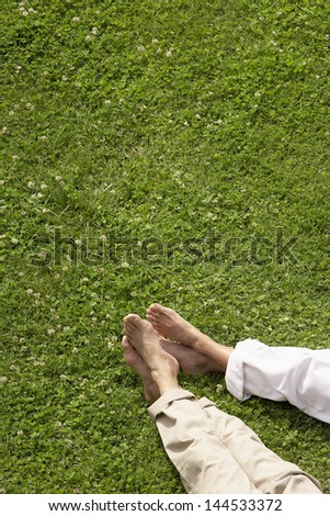 Low section of couple relaxing on grass - stock photo