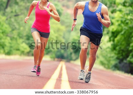 Low section of determined man and woman running on country road. Young couple is in sports clothing. They are representing their healthy lifestyle. - stock photo