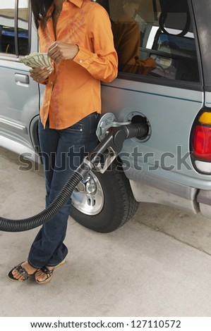 Low section of female counting money while leaning on car at petrol pump - stock photo