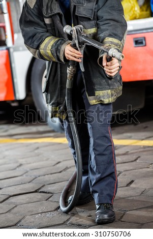 Low section of firefighter holding water hose while standing at fire station - stock photo