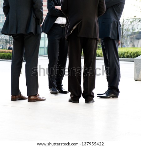 Low section of four businesspeople standing together.