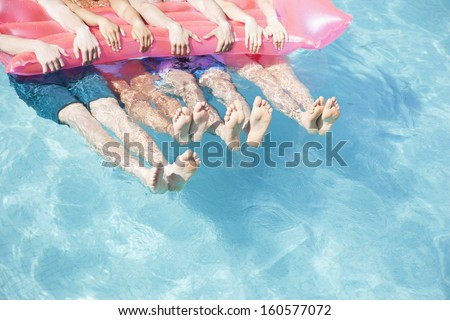 Low section of four friends in pool holding onto inflatable raft with feet sticking out of water - stock photo