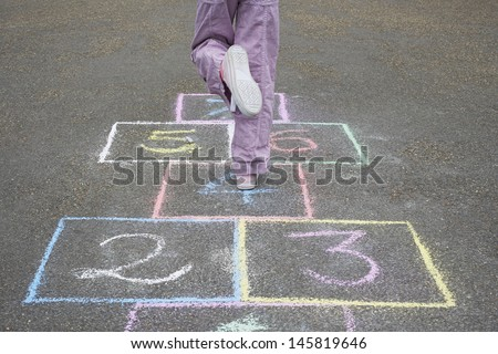 Low section of girl playing hop-scotch in playground - stock photo