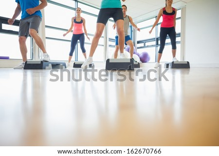 Low section of instructor with fitness class performing step aerobics exercise in gym - stock photo