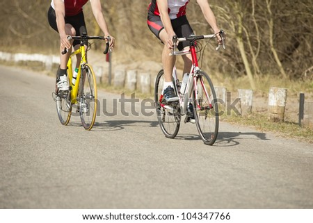 Low section of male athletes riding bicycles on a country road - stock photo