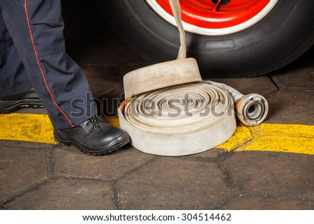 Low section of male firefighter standing by water hose at fire station - stock photo