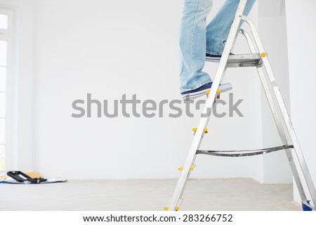 Low section of man on ladder - stock photo