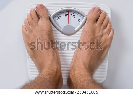Low section of man standing on weight scale - stock photo