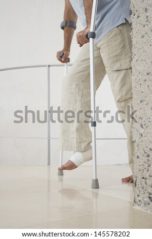 Low section of man with broken leg walking with crutches at home - stock photo
