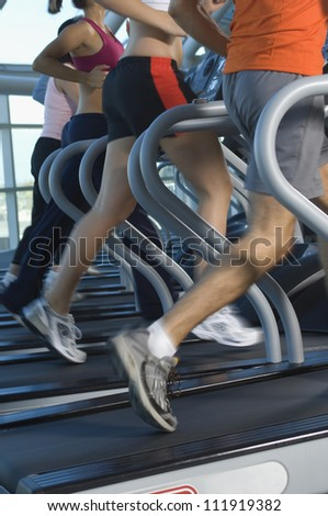 Low section of people exercising on treadmill - stock photo